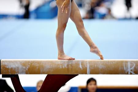 体操選手の足は平均台装置に運動中に見られています。