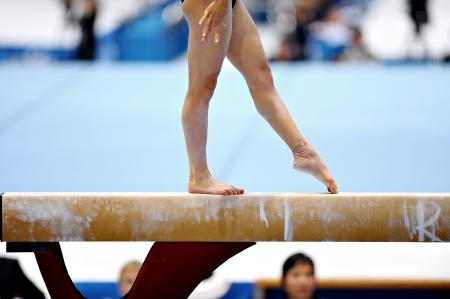 Legs of a gymnast are seen during an exercise on the balance beam apparatus Reklamní fotografie - 22766929