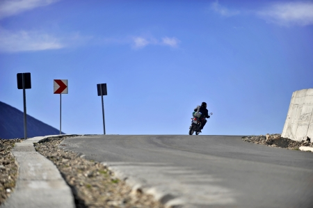 Motorcyclist taking a curve to the right high on Transalpina road photo