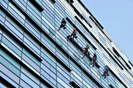 Five window cleaners washing an office building Stockfoto