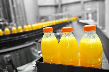 horizontal lines: Botellas de jugo de naranja en la l�nea de montaje de f�brica Foto de archivo