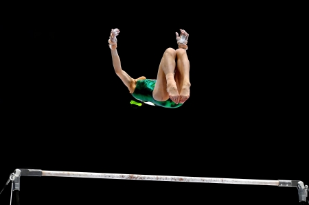 performs: A gymnast performs on the uneven bars apparatus Stock Photo