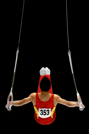 gymnastics equipment: Back view with a gymnast performing on the rings apparatus
