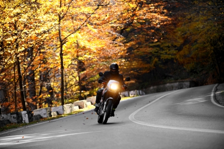 Cheia, Romania - 20 October 2013: A motorcyclist on Cheia road in mid autumn. Cheia is one of the most beautiful motorable roads in Romania.