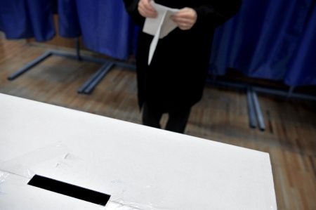 free vote: Hands of a man preparing to cast a vote in the ballot box