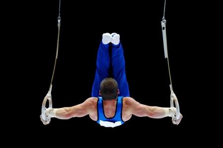 Vista trasera de un gimnasta que se realiza en el aparato de anillos
