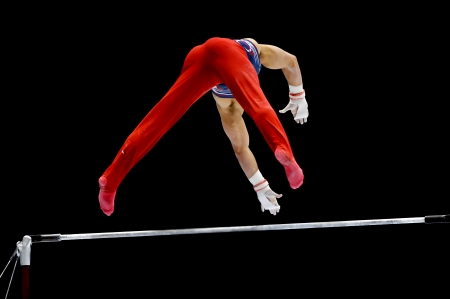 Gymnast performs on the uneven bars apparatus Stock Photo