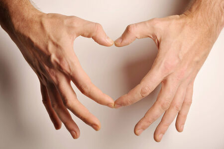 Hands of a man in form of a heart isolated on white  photo