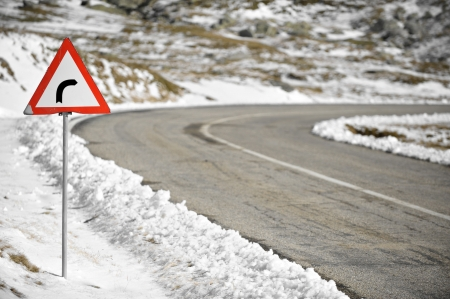 Sharp right curve sign on a mountain road in winter season photo