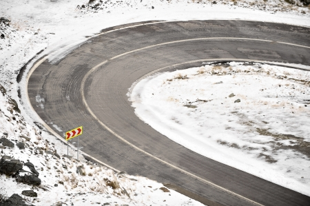 A hairpin turn on a mountain road in winter photo