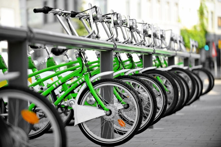 Urban scene with green bicycles for rent in a velo station