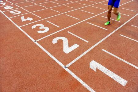 pista de atletismo: Atleta borrosa por una velocidad de obturador de la cámara lenta de cruzar la línea de meta después de la pista de sprint