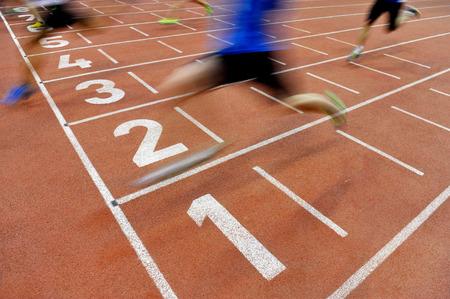 Verschwommene Athleten von einer langsamen Kameraverschlusszeit über die Ziellinie, nachdem Sprintstrecke