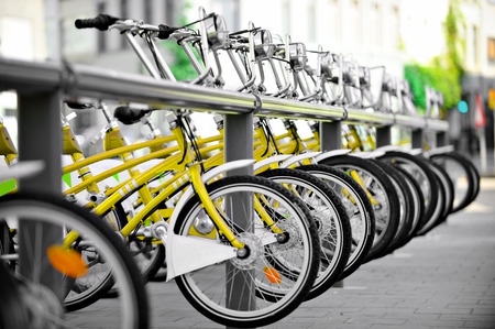velo: Urban scene with yellow bicycles for rent in a public bicycle station Stock Photo