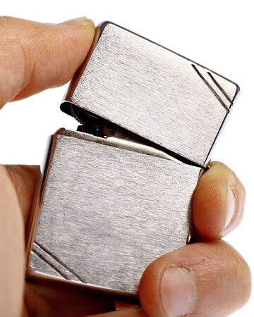 Hand holding vintage metal lighter isolated on white background Stock Photo - 26578306