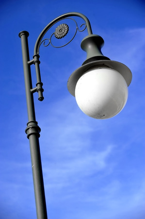 Outdoor public lighting pole with blue sky on background photo