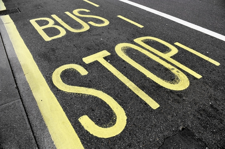 bus stop: Bus stop sign with yellow paint on asphalt