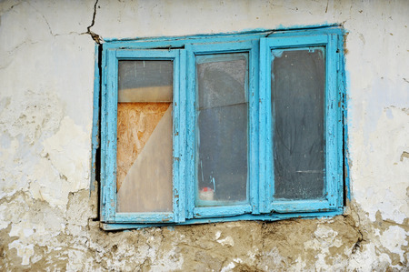 Damaged old traditional adobe house detail with blue window photo