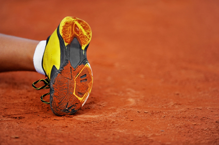Detail with a tennis shoe sole on a tennis clay court photo