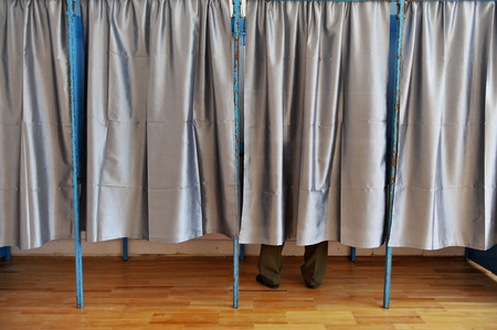 voting booth: A man casting his vote inside a voting booth Stock Photo