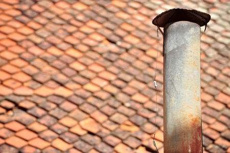 stove pipe: Architecture detail with rusty tin chimney and tile roof on the background Stock Photo