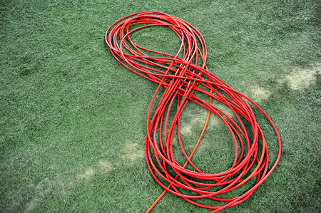 coiled: Television red cable coiled on artificial turf Stock Photo