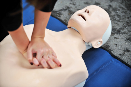 Hands of a woman are seen on a mannequin during an exercise of resuscitation Stock Photo