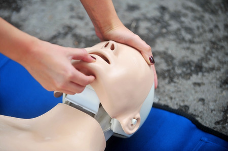 first help: Hands of a woman are seen on a mannequin during an exercise of resuscitation Stock Photo