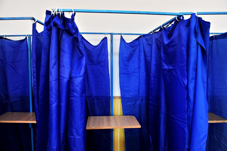voting booth: Voting booths with blue drawn curtains and no people inside