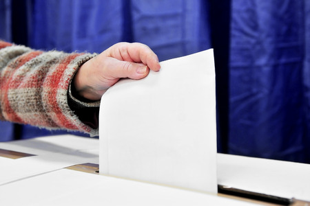 secrecy of voting: Close-up of a person hand putting a vote in the ballot box Stock Photo