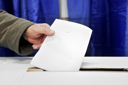 secrecy of voting: Close up of a mans hand putting a vote in the ballot box