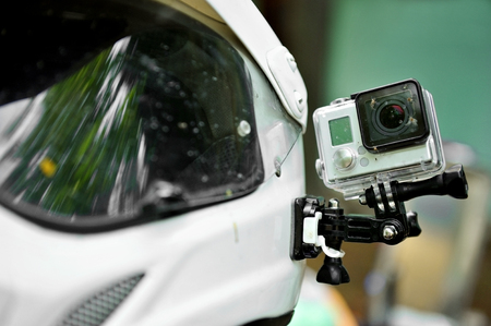 cameras: Action camera with dead insects mounted on a motorcycle helmet Stock Photo
