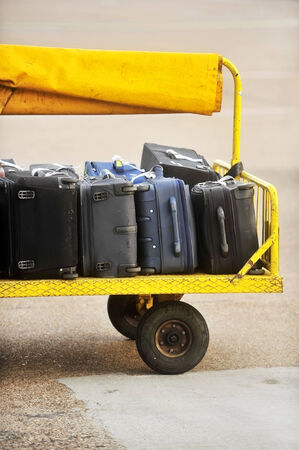 Yellow trolley loaded with luggage on an airport tarmac track photo