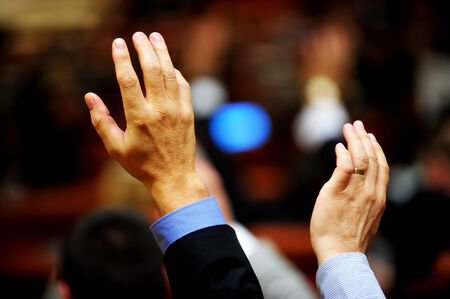 expressing: Detail shot with two raised hands expressing a vote