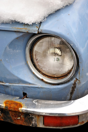 Detail shot with a headlight of an old car in winter time photo