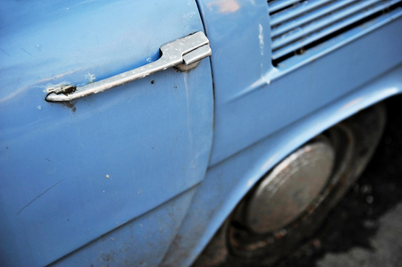 Detail shot with a door handle from an old vintage blue car photo