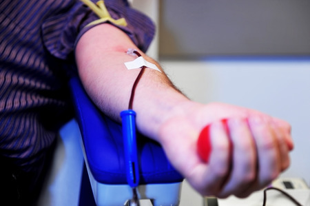 The hand of a blood donor squeezing a medical rubber ball