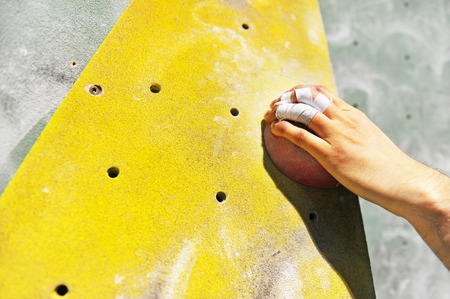 climbing  wall: Detail with climber hand on artificial indoor climbing wall Stock Photo