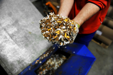 smuggling: Hands of a man holding a heap of destroyed counterfeited cigarettes