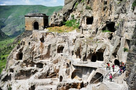 VARDZIA, GEORGIA - JULY 8: Tourists visiting Vardzia ancient cave city on a summer day, on July 8, 2014. Vardzia is one of the main attraction in Georgia. Redactioneel