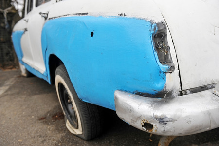 abandoned car: Detalle con una luz trasera que falta de un coche chatarra abandonada