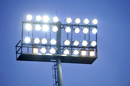 Football stadium spotlights turned on at sunset