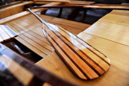 Detail shot with a new wooden paddle in a canoe photo