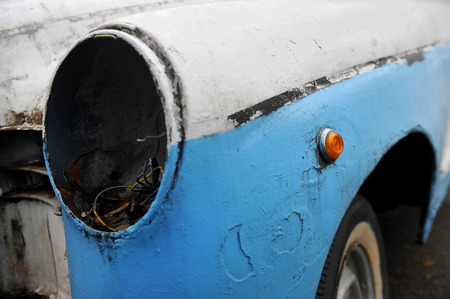 abandoned car: Detalle con un faro que falta de un auto chatarra abandonada