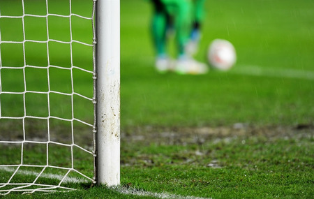 Soccer goal detail on rainy day with goalkeeper preparing for a goal kick in the background