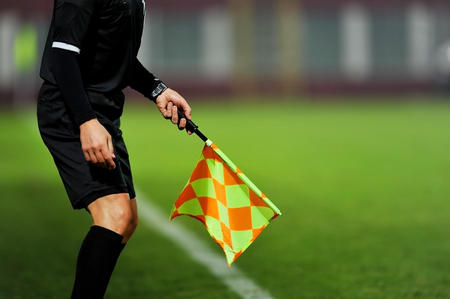 referees: Assistant referees in action during a soccer match Stock Photo