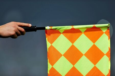 arbiter: Hand of an assistant referee raising the flag during a soccer match