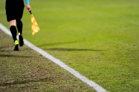 offside: Assistant referees running along the sideline during a soccer match