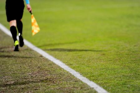 arbitros: �rbitros asistentes se ejecutan a lo largo de la l�nea de banda durante un partido de f�tbol