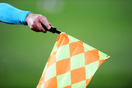 arbiter: Detail with the hand of an assistant referee raising the flag during a soccer match Stock Photo